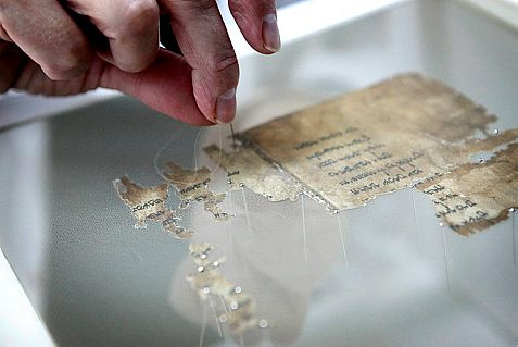 A worker of the Israel Antiquities Authority sews fragments of the Dead Sea scrolls, in a preservation laboratory at the Israel Museum in Jerusalem.