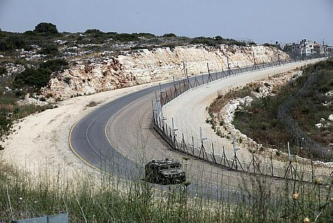 Israeli Defense Forces patrol vehicle drives along a security fence in March 2014.