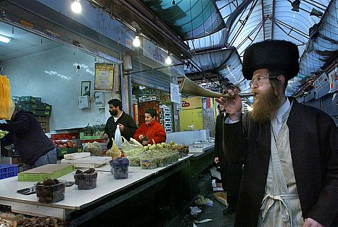 An ultra-orthodox man blowing the shofar to announce the approaching Sabbath in Mahane Yehuda market in Jerusalem.