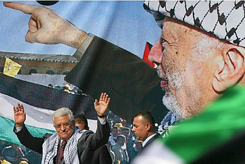 Mahmoud Abbas, acting leader of the PA, speaks in front of a banner of Yasser Arafat.