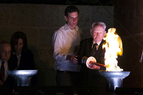 Holocaust survivor Asher Oud (R) lights a torch with his grandson during a ceremony at the Yad Vashem Holocaust Memorial Museum in Jerusalem, as Israel marks the annual Holocaust Remembrance Day on April 27, 2014. Photo by Yonatan Sindel/Flash90