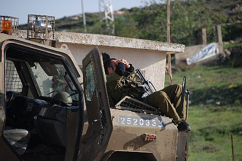 "During one the ""intermissions"" an IDF reserves soldier rests and basks in the sun, as his comrades continue to wage battle inside Jeelazun near Beit El."