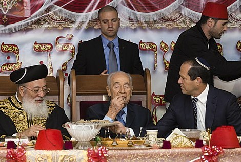 Former Chief Rabbi HaRav Amar, Israeli President Shimon Peres, and Jerusalem Mayor Nir Barkat celebrating the Mimouna, a traditional holiday celebrated by Moroccan Jews at the end of Passover, in Jerusalem on April 21, 2014.