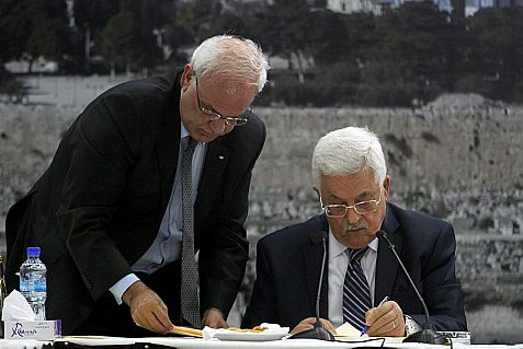 Abbas, with PA negotiator Saeb Erekat looking on, signs an application for the PA to join to U.N. agencies.