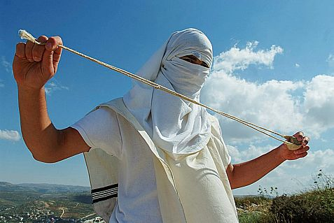 A masked Jewish extremist holds a slingshot as he stands near Mitzpe Yitzhar,