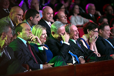 From left, Jerusalem mayor, Nir Barkat, Sara Netanyahu, Prime Minister Benjamin Netanyahu, and former New York mayor Michael Bloomberg, sit in the audience and laugh as American talk show host, Jay Leno (unseen), hosts the Genesis Award ceremony at the Jerusalem Theater, on Thursday, May 22, 2014. Former mayor of New York City, Michael Bloomberg, was given the award.