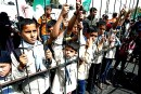 Palestinian boys stand behind mock jail bars during a rally calling for the release of Palestinian prisoners from Israeli jails, in Rafah in the southern Gaza Strip on April 20, 2014.