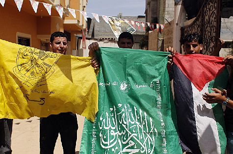 Palestinian Authority Arabs wave the flags of two PA factions, Fatah (yellow) and Hamas (green) as they chant slogans in support of the national reconciliation and the announcement of the formation of a national unity government in Khan Yunis, in southern Gaza on May 29, 2014.