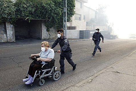 Firefighters evacuate a wheelchair-bound resident whose home is threatened by raging in fire near Jerusalem's Hadassah Ein Kerem Hospital and the neighboring Mt. Herzl, home to Yad VaShem.