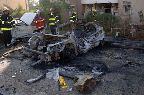 Rescue forces inspect a car after Grad shrapnel hit it in Beer Sheva,November 20, 2012.