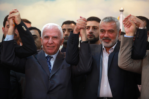 Hamas PM Ismail Haniyeh (R) and Fatah official Azzam Al-Ahmed (L) announce a reconciliation agreement in Gaza City April 23, 2014.
