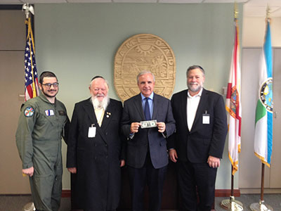 (L-R): Yitzie Rosenberg, Rabbi Pinchas Weberman, Miami-Dade County Mayor Carlos (holding dollar), and David Weberman