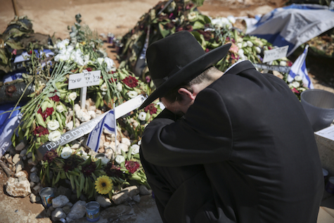 Ultra Orthodox man mourns by the graves of Eyal Yifrach, Gilad Sha'ar and Naftali Fraenkel, two days after their funeral, July 3, 2014