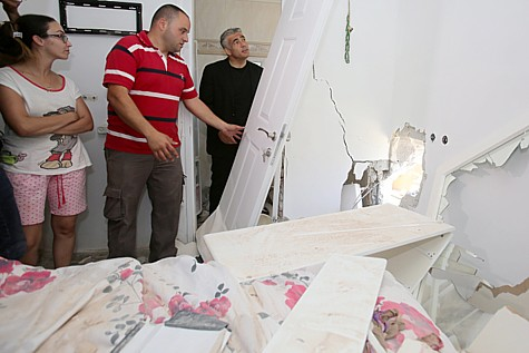 Minister Yair Lapid visits a Sderot home hit by a rocket from Gaza.