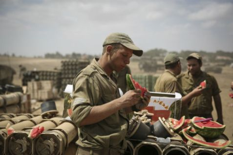 Soldiers on break eat watermelons brought to them by Israeli donors.