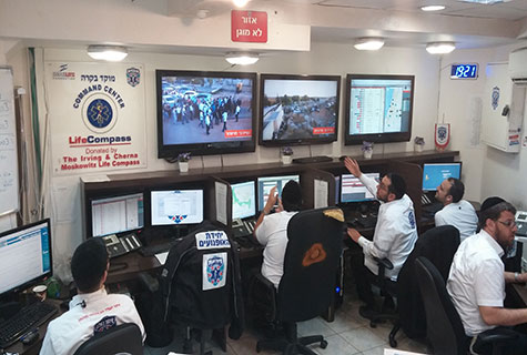 LifeCompass dispatchers monitoring the funeral of Naftali Frankel, Eyal Yifrach and Gilad Shaar in Modiin on Tuesday. Three hundred United Hatzalah volunteers were at the funeral in case of emergencies.