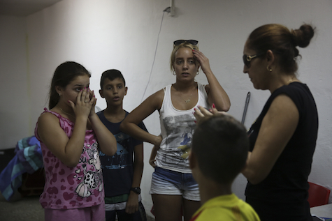 Ashkelon residents gather in bomb shelter, listen to explosions outside.