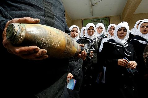 Hamas explosives expert holds a mortar shell as he explains the weapon to schoolgirls.