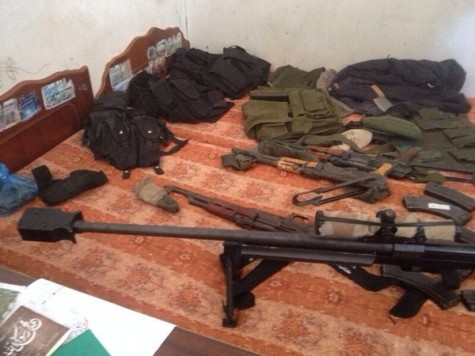 Is a Hamas member who stores weapons in his home a civilian or combatant? Pictured, weapons and ammunition found by the IDF in the bedroom of a Gaza home, July 2014