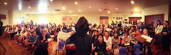 Rebbetzin Chani Lipskar addresses women at communitywide Tisha B'Av women's event.