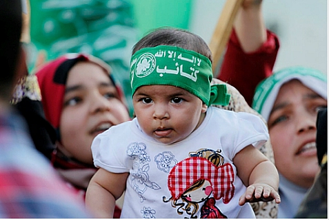 "Baby wearing a Hamas head band attends a Hamas ""victory"" rally in central Gaza City, on August 27, 2014, following the latest cease-fire. Gaza populace celebrated terrorists'  ""victory"" despite obvious damage from Israeli air strikes."