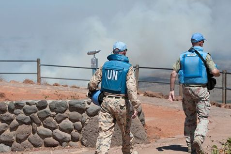 UN troops look at smoke rising from Quneitra on the Syrian side of the Golan Heights.