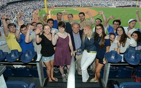 Yankees President Randy Levine and wife Mindy, center, at Yankee Stadium with young men and women planning aliyah and service in the IDF.
