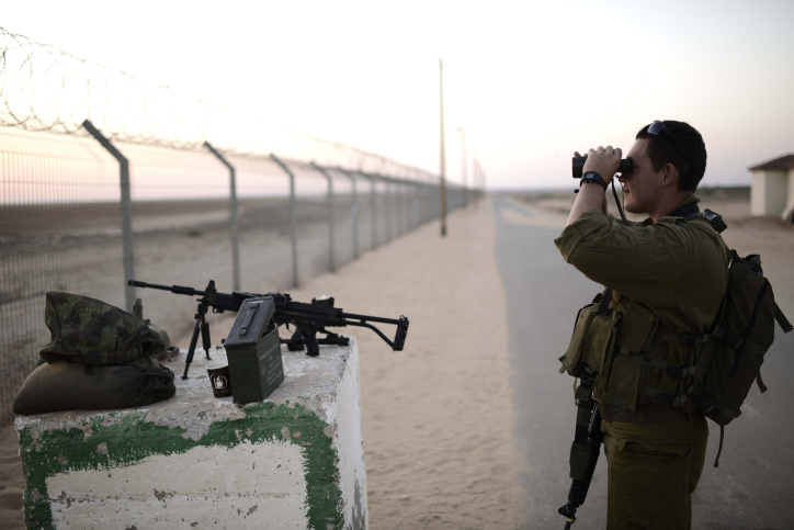 IDF reserve soldier stands guard near the Israel-Gaza border, August 7, 2014.