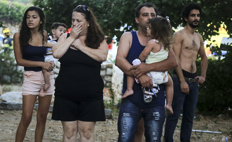 Residents look in shock after a rocket hit their home in Ashkelon, August 26, 2014. Passersby were hurt by broken glass, while many others were treated for shock.