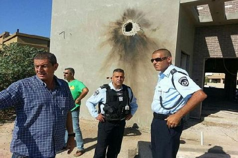 Police inspect a home that was damaged in a Qassam rocket barrage from Gaza on Friday, August 8, 2014. Miraculously, no one was in the house at the time.