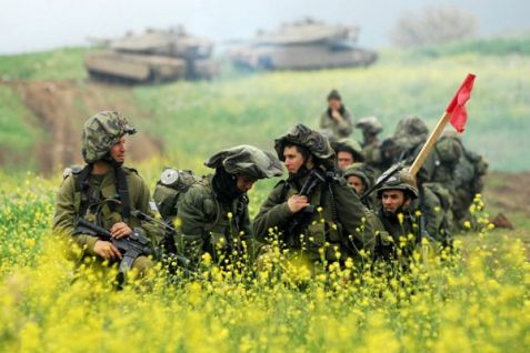 IDF infantry soldiers on the Golan Heights, with tanks in the background.