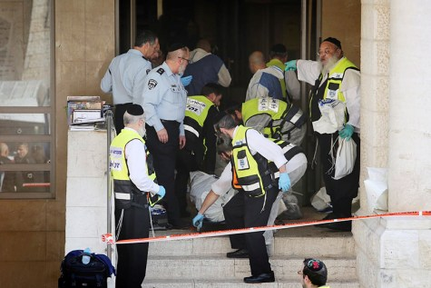 Police remove casualties from a Har Nof synagogue after two Jerusalem Arabs butchered four Jews to death.