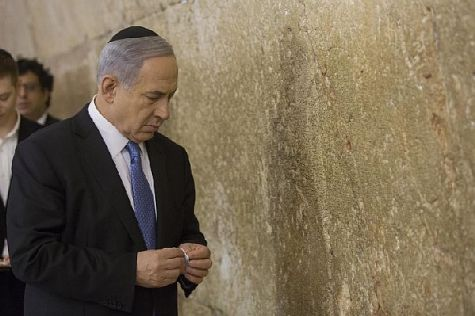 Prime Minister Binyamin Netanyahu prepares to place a note in the Western Wall.