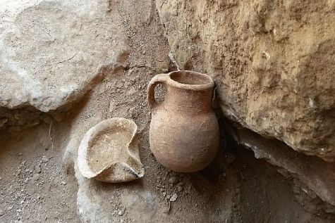 An oil lamp and a ceramic jar that date to the Iron Age, which were discovered in the cave.