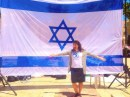 Jewish Press bloger, Jordana Brown, standing in front of  her nation's flag