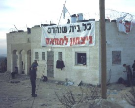 "A home slated for demolition in Amona in 2006. The banner reads: ""Every demolished home – Hamas victory."""