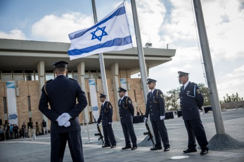 The Knesset Honor Guard lowers the Israeli flag at half-mast during a ceremony in memory of Former Israeli President Shimon Peres at the Knesset, the Israeli parliament in Jerusalem on September 28, 2016.