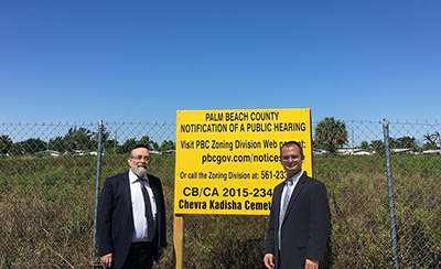 Rabbi Zohn (Left) and Rabbi Lyons at the cemetery site with the signs about the public hearing.