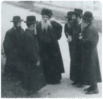 Simcha Dinter (far right, clutching a religious text) in the company of the Belzer Rebbe and his aides. (Marienbad, Czechoslovakia, 7 August 1923.)