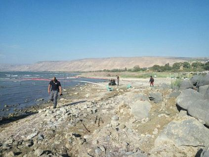 Searching along the beaches of Lake Kinneret for unexploded ordnance.