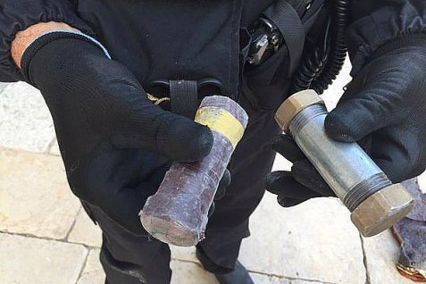Police sapper holds pipe bombs found  Sunday at the entrance to the Al-Aqsa mosque on the Temple Mount.