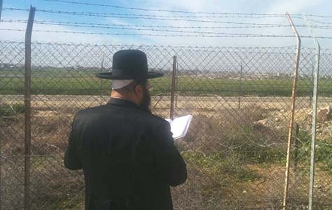 Rabbi Shriki praying at the Gaza border fence / Source: Facebook