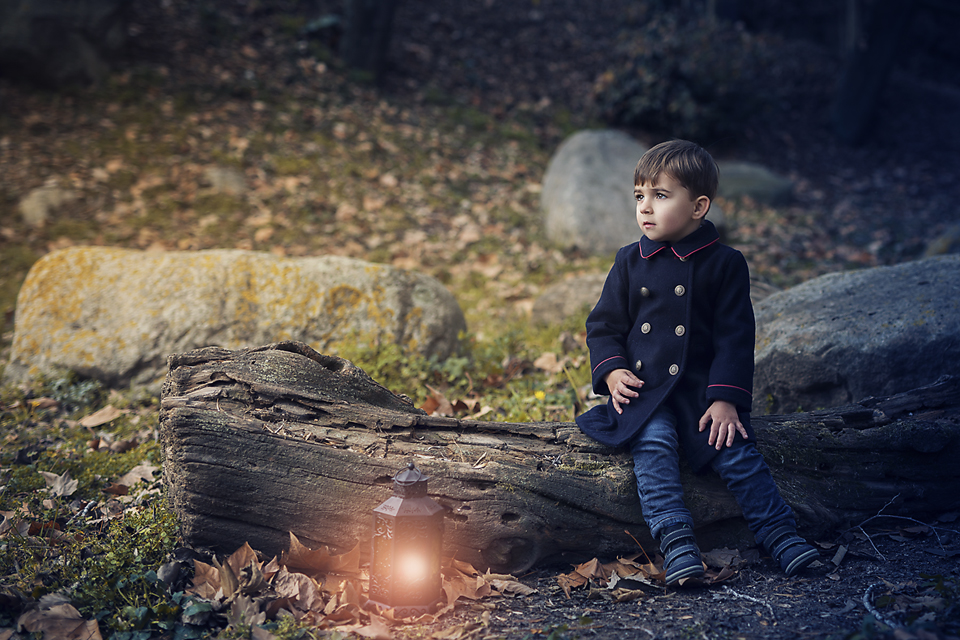 Baby sitting with a lamp in the forest of Montseny
