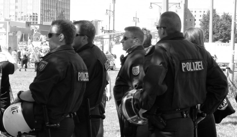 Hier ist ein Bild mehrerer Polizisten bei einer Demonstration zu sehen. Die Gesichter sind nicht erkennbar, die Beamten stehen der Kamera abgewandt