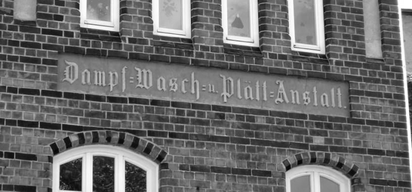 """Hier ist ein Bild aus Wismar zu sehen, eine geklinkerte Hausfassade (Backstein-Gothik) mit einer alten, eingemeißelten Schrift. Die Inschrift lautet: """"Dampf- Wasch und Plättanstalt"""""""