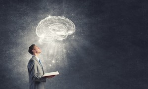 Shocked businessman holding opened book with brain picture