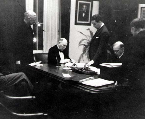 Lord Riverdale (on the left) and W.L. Mackenzie King (on the right) signing the BCATP Agreement on December 17th, 1939.