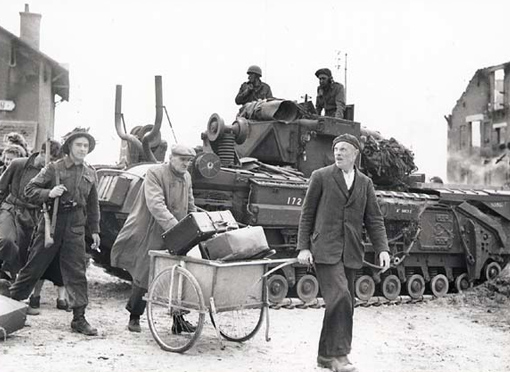 Helped by a sergeant, French civilians walking by a tank in Bernières.