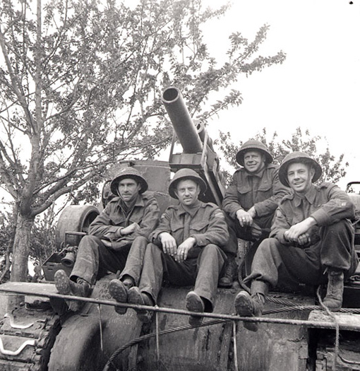 Bdr. L.A. Boyle, Gunner H.W. Embree and Gunner L. Armstrong, 14th Field Regiment, RCA, seating on a Priest self-propelled gun in Normandy, 20 June 1944.