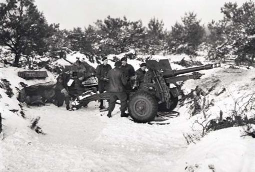 "Members of ""B"" Troop, 5th Field Regiment, firing 25-pounder near Malden, Holland, 1 February 1945. From left to right: Sergeant Jack Brown, Bdr. Joe Wilson, Gunners Lyle Ludwig, Bill Budd, George Spence, and Bill Stewart."